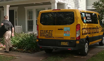 Stanley Steemer van parked in front of a house