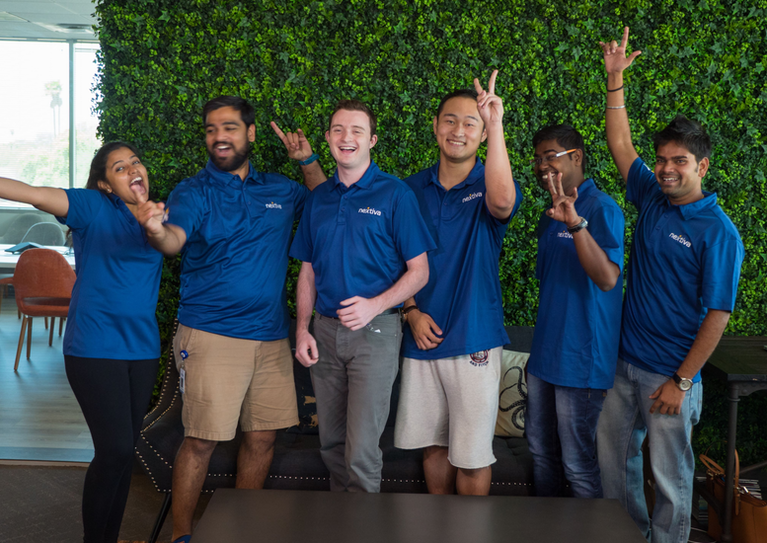 Nextiva interns posing exuberantly in front of living wall.